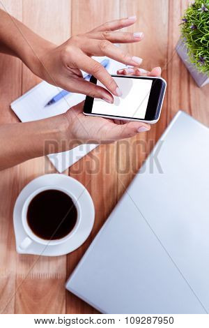 Overhead of feminine hands using smartphone with coffee, notebook and laptop on table