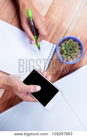 Overhead of feminine hands holding smartphone and taking notes