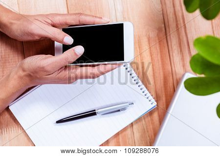 Overhead of feminine hands using smartphone with notebook and laptop on table