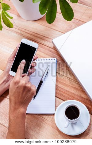 Overhead of feminine hands using smartphone with notebook, laptop and espresso on table