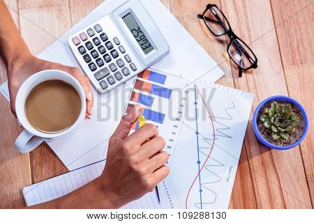Woman doing some banking at home on wooden desk
