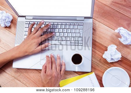 Part of hands typing on laptop on wooden desk