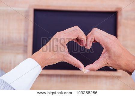 Hands making heart shape with blackboard on background