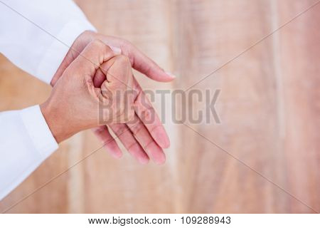 Close up view of hands on wood desk at work