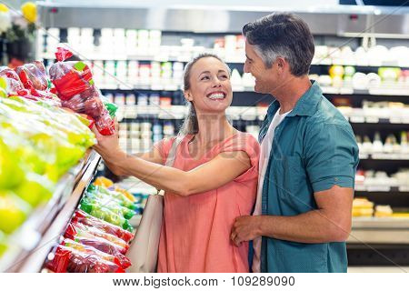 Happy couple at the supermarket smiling to each other
