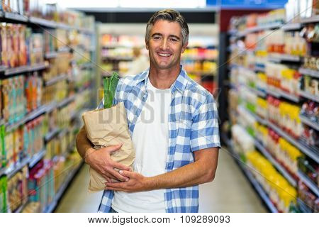 Smiling man holding grocery bag in supermarket