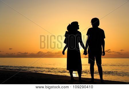 romantic couple with little child at sunset tropical beach