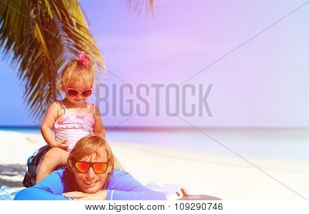 Happy father and cute little daughter at beach