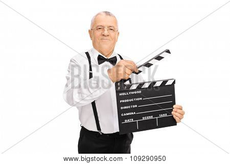 Elegant mature man holding a movie clapperboard and looking at the camera isolated on white background