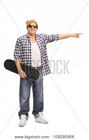 Full length portrait of a cool senior holding a skateboard and pointing towards the right with his hand isolated on white background