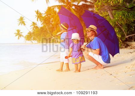 Father and two kids at beach with umbrellas