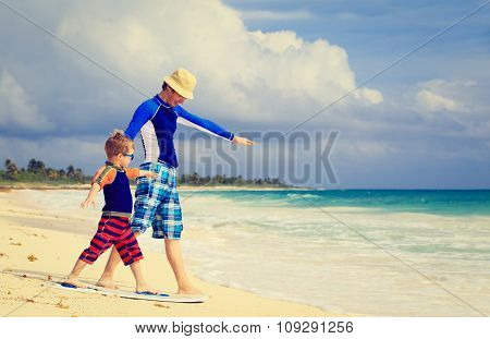 father and little son practicing surfing positin at beach