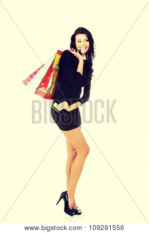 Full length woman with a lot of shopping bags.