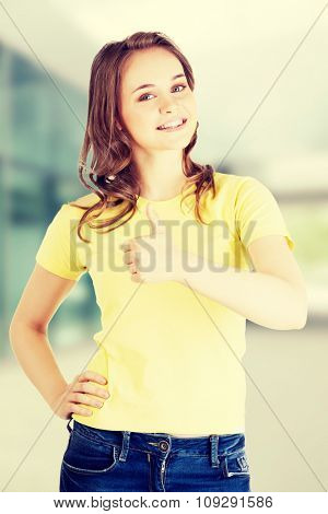 Beautiful teen woman in casual clothes gesturing thumbs up