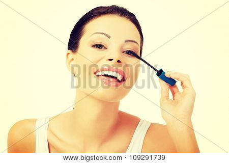 Portrait of a woman applying make up.