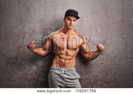 Shirtless street thug stretching a metal chain over his shoulders and leaning against a rusty gray wall
