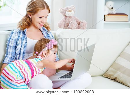 Happy Family Pregnant Woman And Child With A Laptop At Home