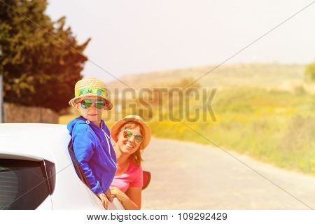 happy mother and son travel by car in summer mountains