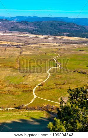 Aerial view of fields, mountains and  road in the countryside