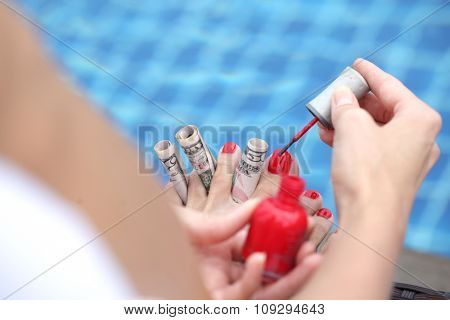 Woman painting nails using dollar bills sitting outdoors by the pool