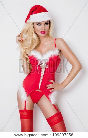 Beautiful sexy blonde female model snowflake dressed as Santa Claus erotic red lingerie with white f