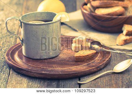 Metal Cup Of Tea, Brown Sugar, Crackers And Lemon