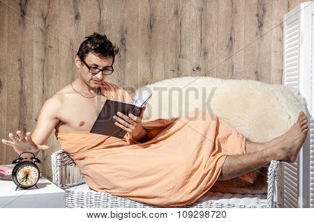Man Reading On Couch When Alarm Clock Rings