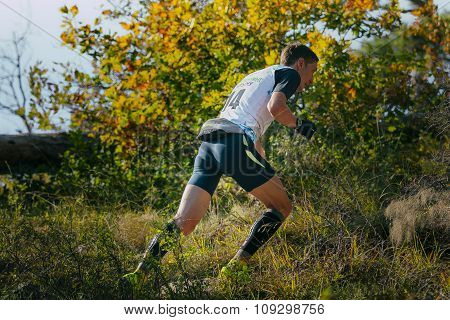 young male runner running uphill, around autumn landscape