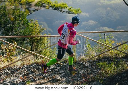 young woman athlete running on mountain trail. in background of mountain valley
