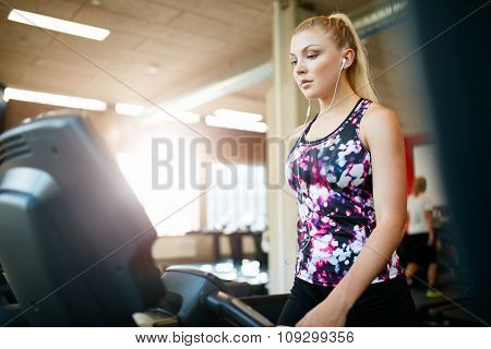 Young Woman Exercising On The Treadmill