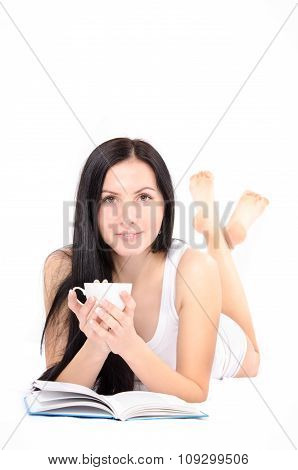 Young beautiful woman drinking coffee lying in bed