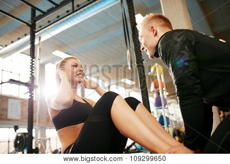 Female Doing Sit Ups With Her Fitness Trainer