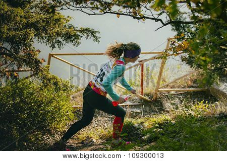 girl athlete running through forest, in her hands a bottle of water isotonic
