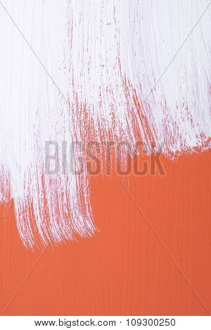 Orange Board Being Roughly Painted With White Paint