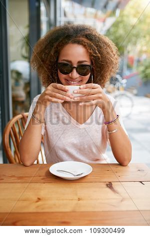 African Woman Drinking Coffee At Sidewalk Cafe