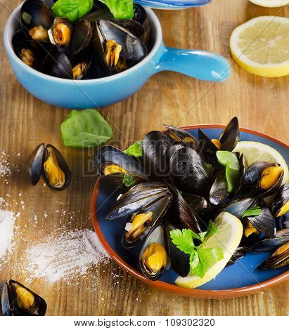 Plate Of Steamed Mussels On A Wooden Background.