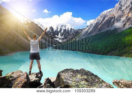 Hiker standing with raised hands near the beautiful mountain lake