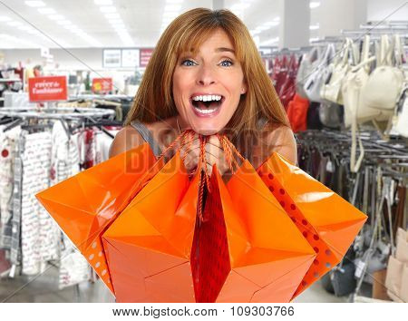 Shopping woman with gifts in a shopping mall .