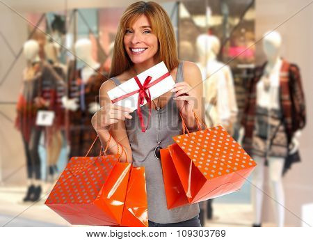 Shopping woman with envelope and gifts in a shopping mall.
