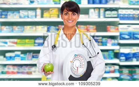 Doctor woman with scales and apple over health care background.