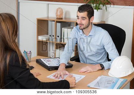 Happy Young Woman Discussing With Consultant In Office