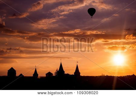 View on the castle in Kamianets Podilskyi and black air balloon during sunset. Ukraine