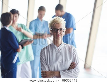 female doctor with glasses and blonde hairstyle  standing in front of team  in background, group of medical staff at hospital