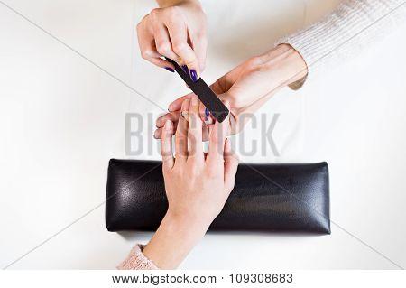 Image of hands polishing fingers on towel