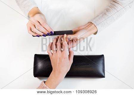 Manicure master nail file work on  pointing finger