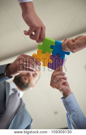 business people group assembling jigsaw puzzle and represent team support and help concept, top view perspective at modern bright office interior