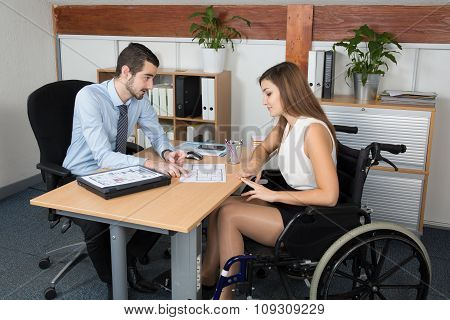 Woman In Wheelchair And Man Sales Representative At Work