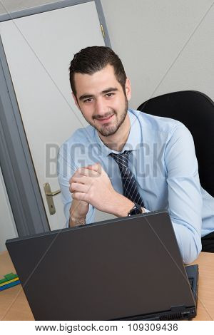 Business Man In Office Sitting At His Desk