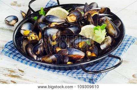 Pot Of Gourmet Mussels  Garnished With Lemon Slices.
