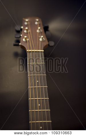 Headstock,fret bordfret,stuners of guitar acoustic isolate on black ground.